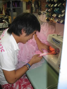 Lehigh University Costume Shop - image of student sewing large pink petticoat